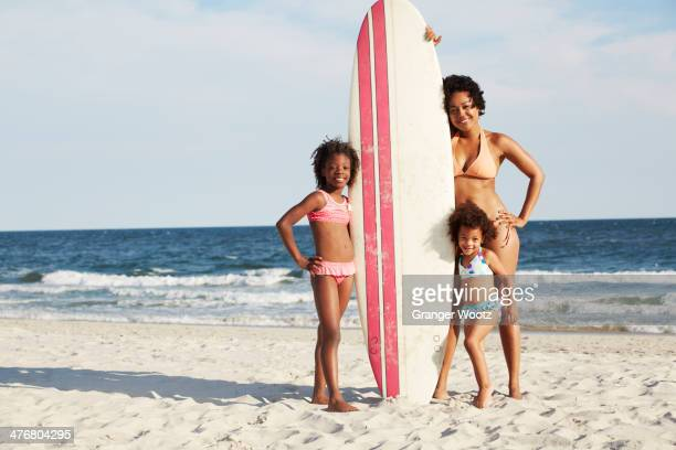 Mother and daughters with surfboard on beach