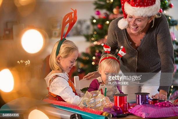 Mother and daughters wrapping Christmas presents