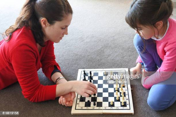 Mother and daugther play chess together