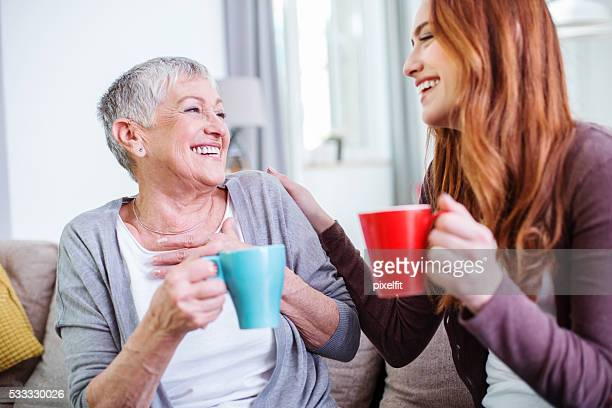 Mother and dauther having hot drinks together