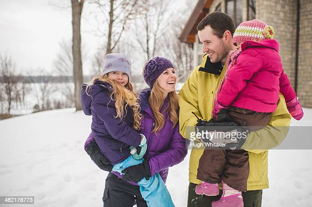 Mother and father carrying daughters in snow