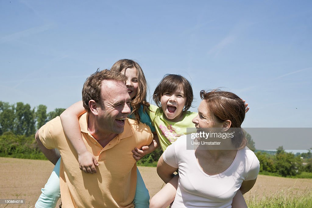 Mother and father carrying their children piggyback across a field : Stock Photo