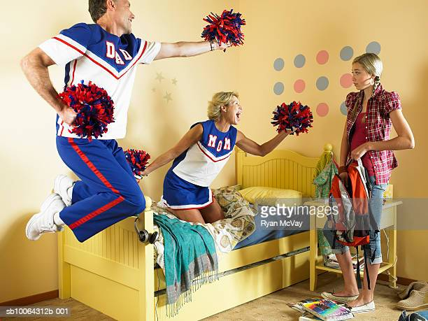 Mother and father dancing with pom poms looking at daughter (13-14)