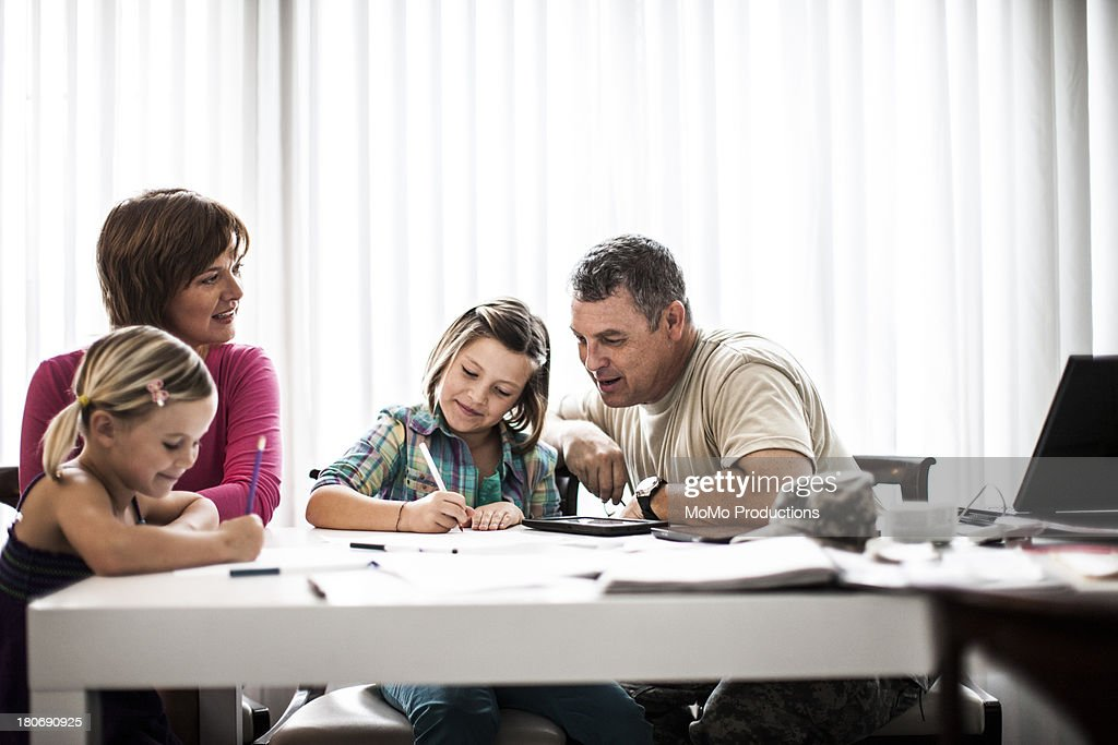 mother and father helping daughters with homework : Stock Photo