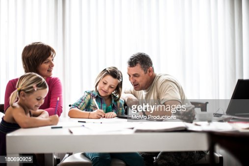 mother and father helping daughters with homework