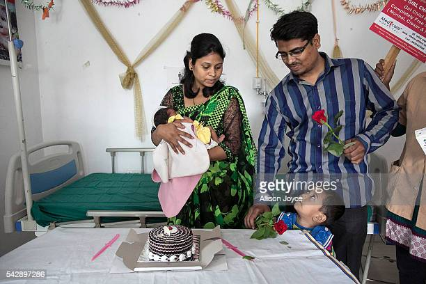 A mother and father hold their newborn girl during a celebration for newborn baby girls at the Medicare Hospital June 22 2016 in Pune India Dr Ganesh...