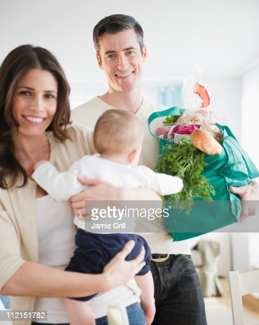 Mother and Father holding baby and groceries : Stock Photo