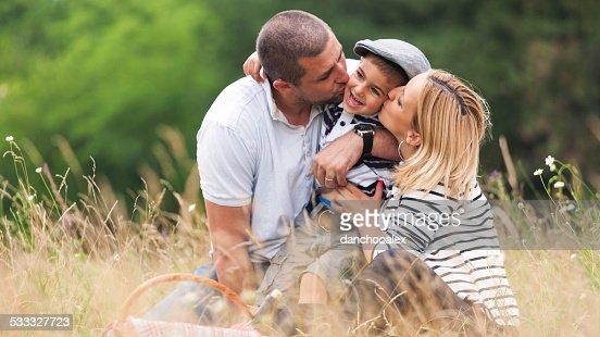 母と父、少年にキスをする