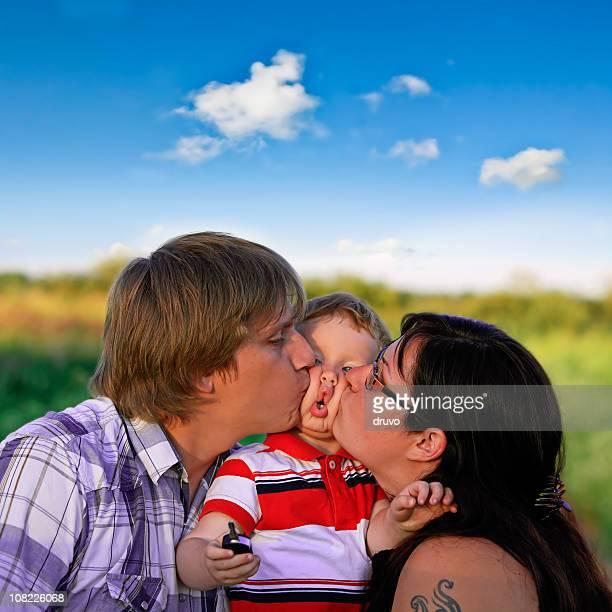 Mutter und Vater Küssen Jungen Sohn auf Wange außerhalb