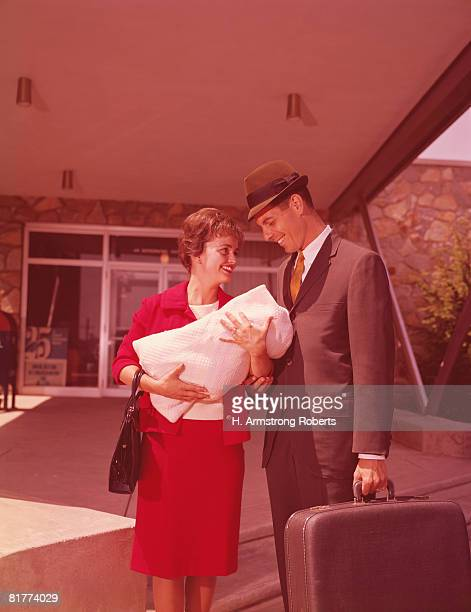 Mother and father leaving hospital with newborn baby.