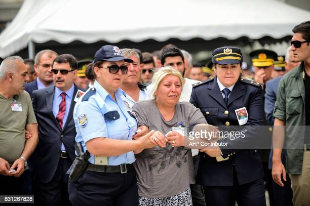 Mother and father of Turkish police officer Sinan Acar killed last night mourn during his funeral ceremony at Istanbul's police department...