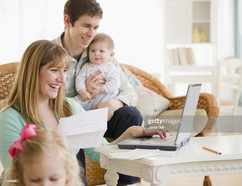 Mother and father paying bills with family : Stock Photo