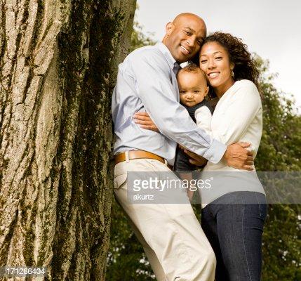母、父、赤ちゃんで遊ぶ少年の公園