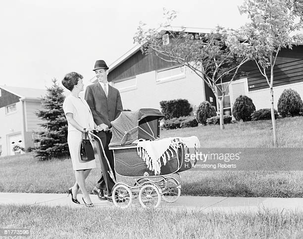 Mother and father pushing baby in pram.