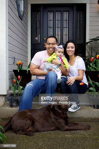 Mother and father sitting on front stoop with baby girl and dog
