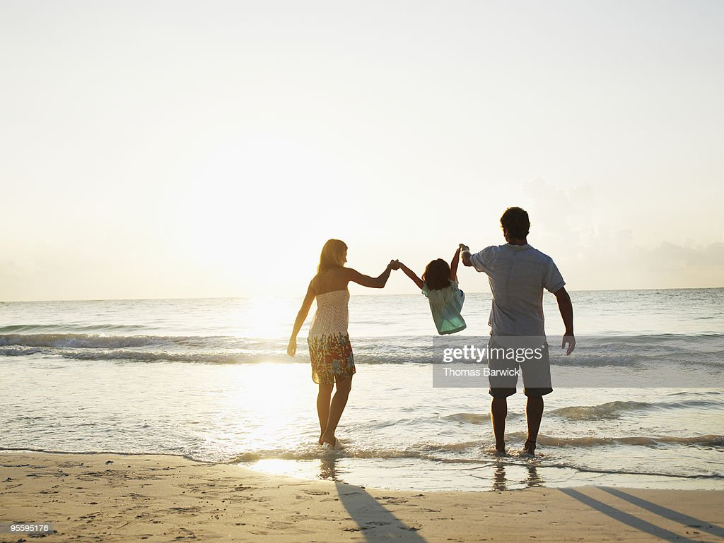 Mother and father swinging daughter by arms : Stock Photo