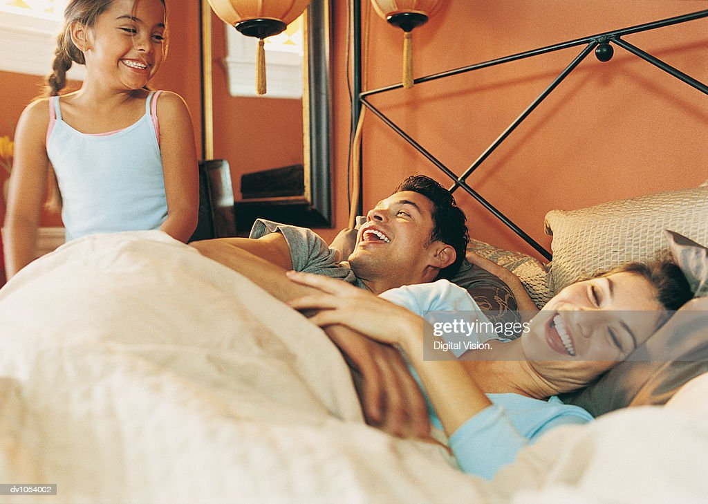 Mother and Father Waking Up with Their Daughter in a Bedroom : Stock Photo