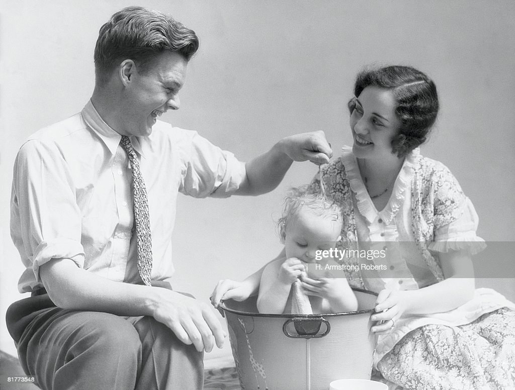 Mother and father washing baby, father squeezing water from flannel onto baby's head. (Photo by H. Armstrong Roberts/Retrofile/Getty Images) : Stock Photo