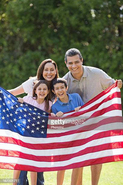 Mother And Father With Children Holding American Flag