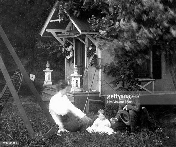 Mother and father with their baby in front of the backyard playhouse