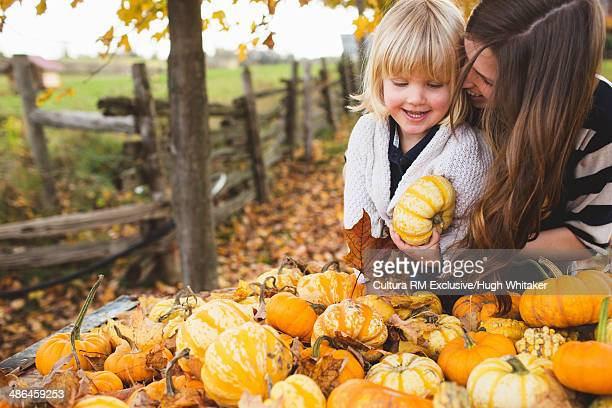 Mother and female toddler choosing autumn squashes