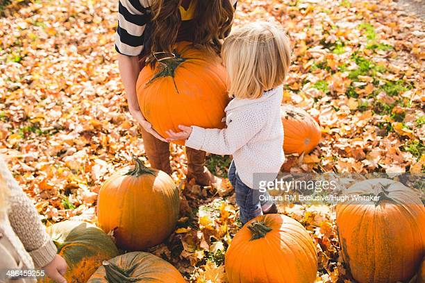 Mother and female toddler lifting a pumpkin