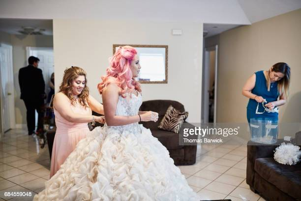 Mother and friend helping young woman get dressed in gown for quinceanera