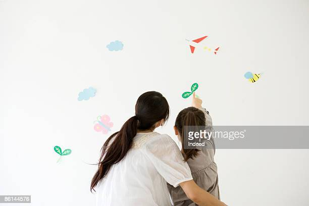 Mother and girl pointing to crafts on wall