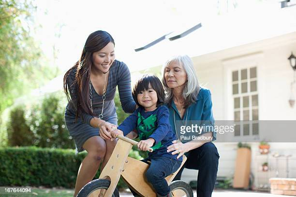 Mother and grandmother pushing boy on tricycle