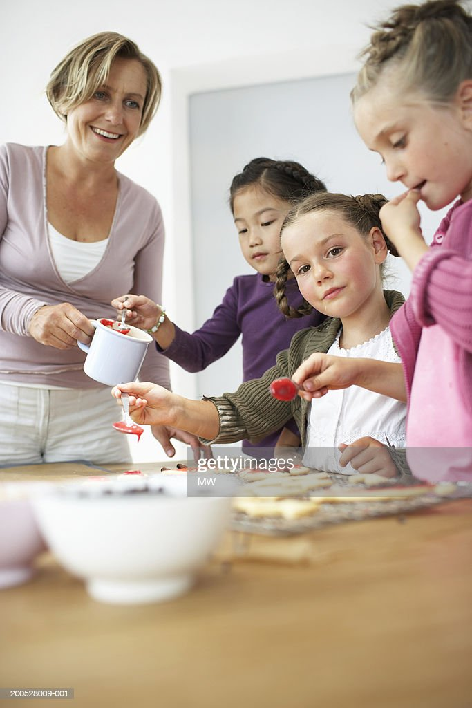 Mother and group of girls (6-8) icing biscuits, low angle view : Stock Photo