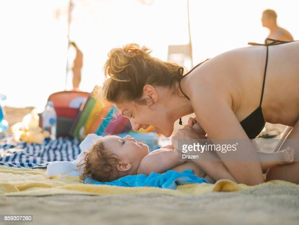 Mother and her baby girl on the beach in summer