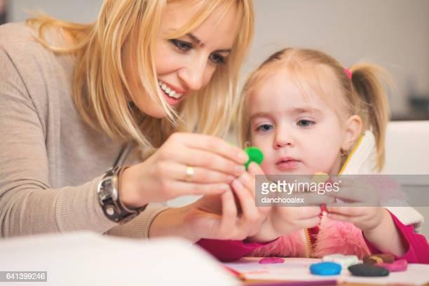 Moeder en haar babymeisje spelen met plasteline
