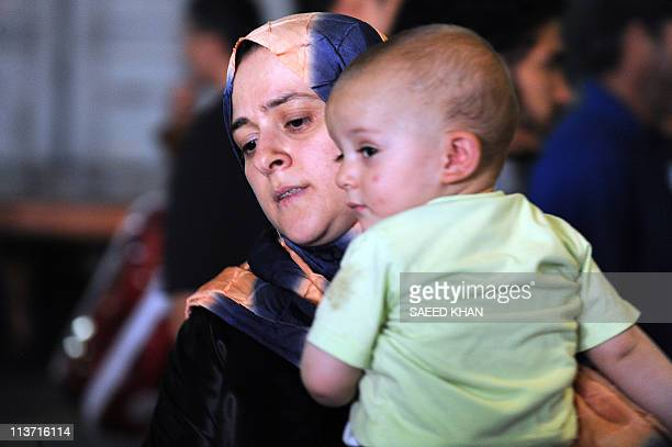 A mother and her child evacuated from the besieged Libyan city of Misrata prepare to get off a ship on May 5 2011 as the vessel carrying 800 migrants...