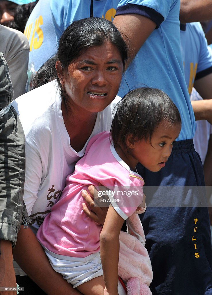 A mother and her child queue up as they try to enter the evacuation centre for food distribution inside a sports complex in Zamboanga on the southern Philippine island of Mindanao on September 20, 2013. Philippine security forces killed eight Muslim rebels on September 20 as they hunted the remnants of a guerrilla force hiding in homes of the major city and believed to be holding hostages.