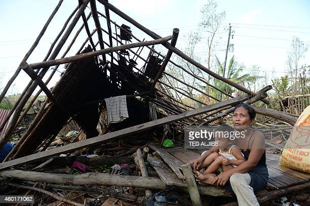 A mother and her child sits next to their house destroyed at the height of Typhoon Hagupit at a village along a highway in San Julian town Eastern...