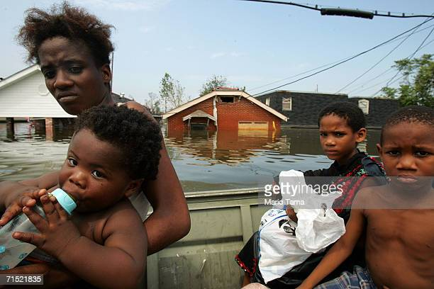 A mother and her children are rescued by boat from the Lower Ninth Ward during the aftermath of Hurricane Katrina August 30 2005 in New Orleans...