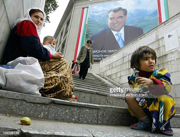 A mother and her children beg in a pedestrian underpass as a picture of Tajik President Emomali Rakhmonov is featured on a building in Dushanbe 23...