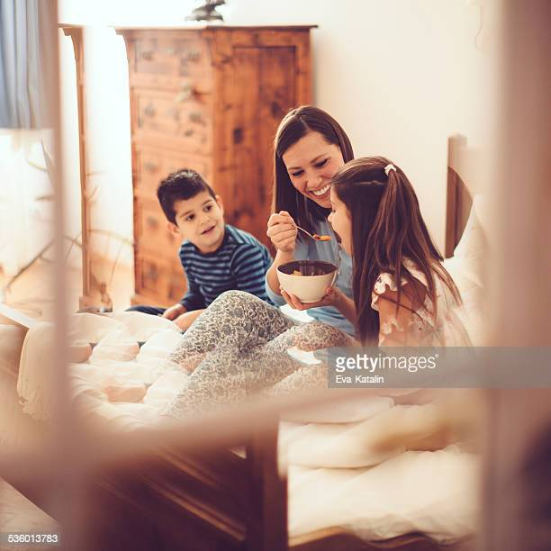 Mother and her children having breakfast in the bedroom