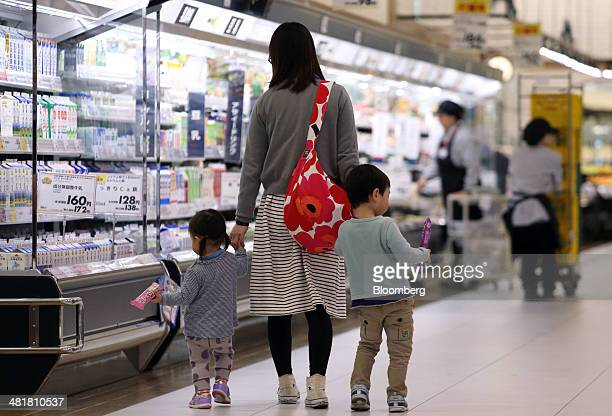 A mother and her children walk through an Aeon Co supermarket in Chiba Japan on Tuesday April 1 2014 Japan's economy will probably withstand a sales...