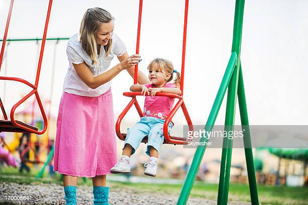 Mother and her cute daughter enjoying outdoors on a swing.