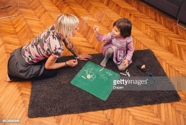 Mother and her daughter chalk drawing on blackboard at home, having joy and unforgettable moments