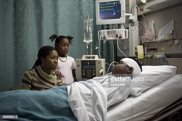 Mother and her daughter looking at a teenage boy in the hospital