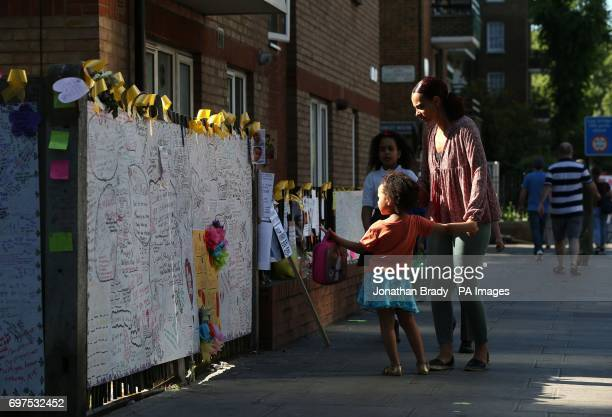 A mother and her daughter pause to look at a wall of remembrance at the junction of Silchester Road and Bramley Road in west London near to the...