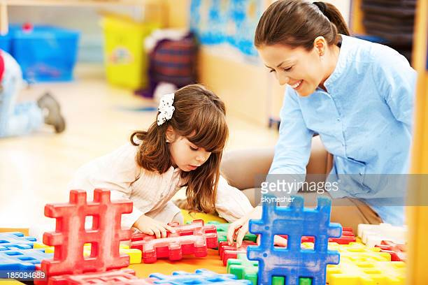 Mother and her daughter stacking blocks