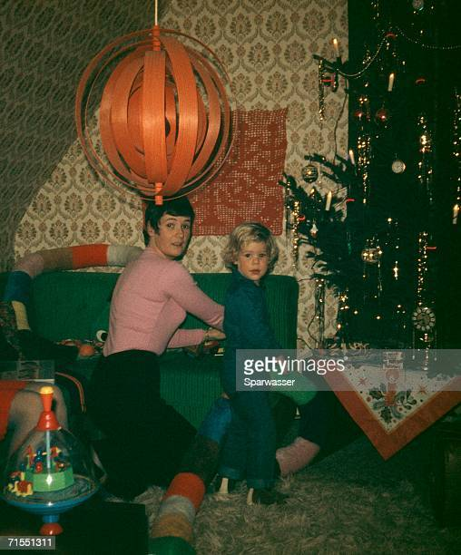 A mother and her daughter standing beside a Christmas tree