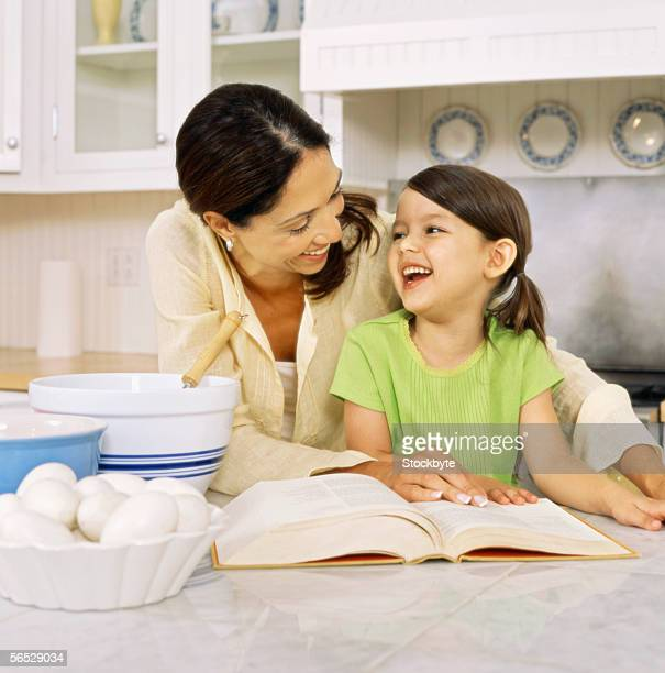 mother and her daughter standing in the kitchen