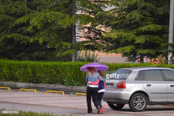 A mother and her daughter walk on the road under rain during summer time in Ankara Turkey on June 21 2017