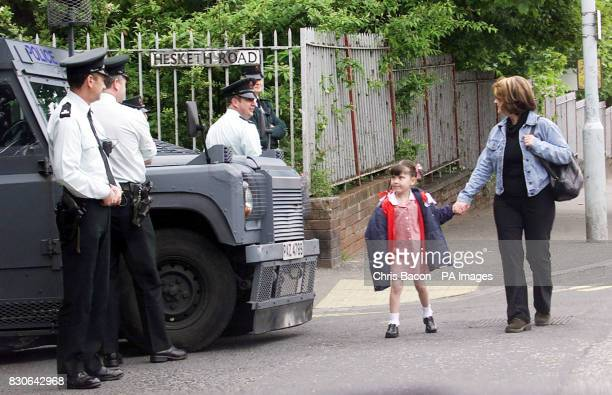 A mother and her daughter walk past police when they are forced to take an alternative route to school away from a Loyalist area where there was over...