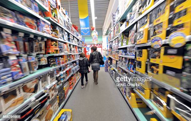 A mother and her daughter walk past the shelves of La Grande Recre toys departement store in the French northern city of BruaylaBuissiere on November...