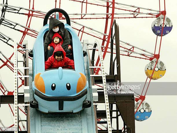 A mother and her daughters enjoy a roller coaster of cartoon charactor Mudkip of Pocket Monster before a Ferris wheel at the 'Pokemon The Park 2005'...
